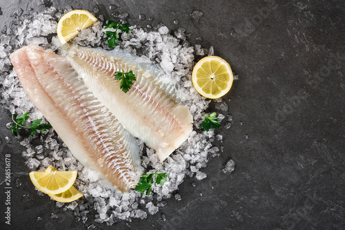 Valokuvatapetti Fresh raw fillet white fish Pangasius with spices on ice over dark stone background