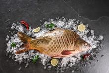 Fresh Raw Whole Mirror Carp Fish With Spices, Lemon On Ice Over Dark Stone Background. Creative Layout Made Of Fish, Seafood, Top View, Flat Lay