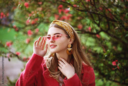 Fotografia Outdoor close up portrait of young beautiful fashionable happy smiling girl with