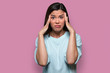 Isolated facial expression of a worried, concerned, fearful, regretful woman, expressing distress and inner conflict, pink background