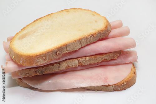 Obraz na plátně  panino a fette italiano con prosciutto cotto su sfondo bianco, italian sliced sa