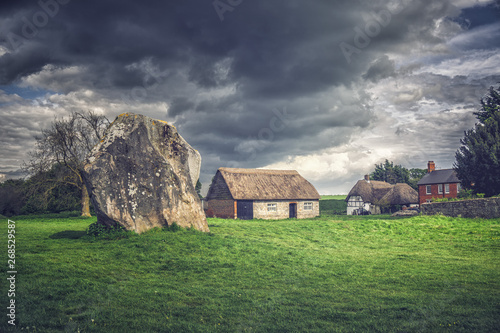 Photographie Dramatic clouds and cottage in Avebury Stone Circles, England.