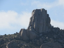 View Of Tom's Thumb From A Distance With Silhouettes Of Unrecognizable People Seen From The Trail In The McDowell Sonoran Mountain Range