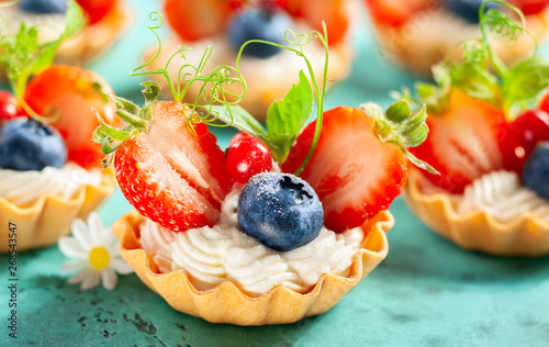 Foto op Plexiglas Bakkerij Summer berry tartlets with cream and fresh berries.