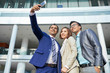 Smiling businessman making selfie portrait together with his colleagues on mobile phone while they standing near the office building outdoors