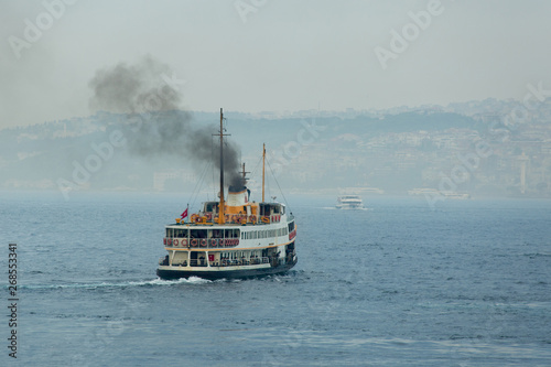 Ferry boat sails on foggy weather and smoke coming from its chimney Canvas Print