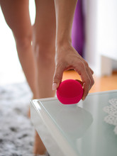 The Young Woman From The Table In The Living Room Takes A Pink Sonic Facial Cleaner Brush Machine. Girl Holding With One Hand  Electronic Silicone Massager For Facial Usage.