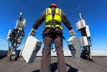 Professional Industrial Climber In Helmet And Uniform Holds Telecomunication Equipment In His Hand And Antennas Of GSM DCS UMTS LTE Bands, Outdoor Radio Units, Optic Fibers, Power Cables Are Installed