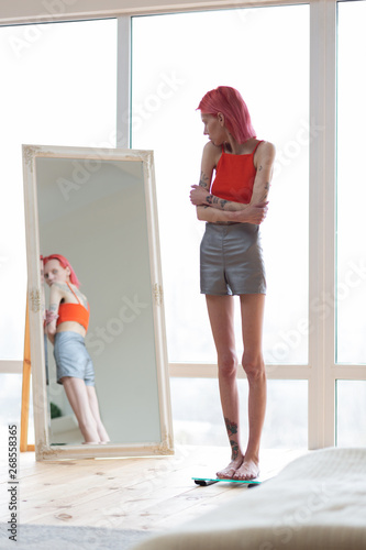 Photo Skinny unhealthy woman wearing shorts and top looking into mirror