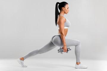 Fitness žena radi vježbe za ispadanje za vježbanje mišića nogu. Aktivna djevojka koja izvodi iskorak naprijed s jednom nogom naprijed, na sivoj pozadini