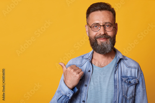 Valokuva  Happy optimistic handsome middle aged male with beard pointing aside with thumb and looking at camera, smiling man in denim jacket and gray t shirt