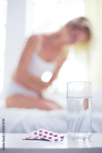 Fototapety, obrazy: Young beautiful woman with pills lying on bed in bedroom