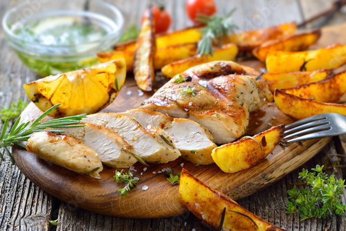 Foto Gegrilltes zartes Hähnchenbrustfilet mit Zitronen-Dip und Rosmarin Potato Wedges