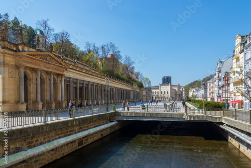 Fotografie, Obraz  Outdoor sunny view above Tepla river, and Mill Colonnade, the largest Renaissance colonnade in town, next to promenade on riverside with full of tourists in Karlovy Vary, Czech Republic