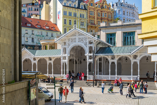 Fotografie, Obraz  Outdoor sunny view of tourists walk on promenade in front of Market Colonnade, Swiss style carved wooden colonnade arbour pavilion, and colorful buildings in Karlovy Vary, Czech Republic