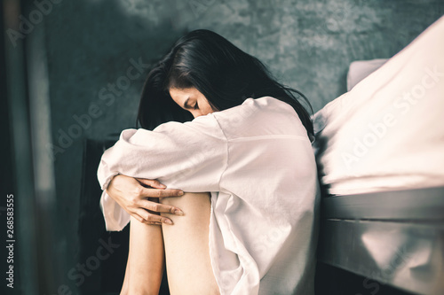 Foto depress Asian woman sitting in bedroom feeling lonely and sad