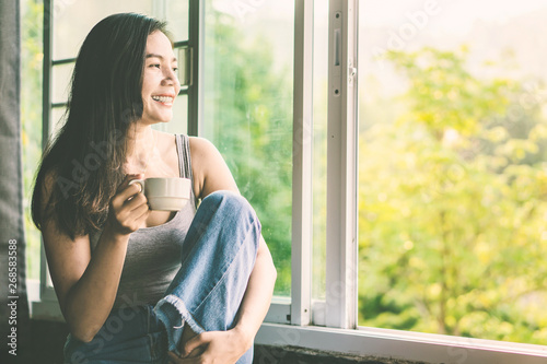 Photo sur Toile The happy Asian woman drinking hot coffee next to the window smiling with nature background