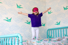 A Toddler Aged Girl Having Fun And Jumping On The Bed In Her Bedroom.