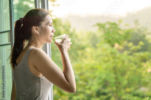 Leinwand Poster Asian woman drinking clean water in the morning next to the window with nature b