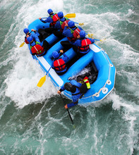Team Of People White Water Rafting - View From Above A Raft In Rapids