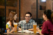Group of asian friends hanging out talking together drink pint glass of beer on Friday night in relaxing after work TGIF concept. Attractive young asian join happy hour night party at bar restaurant.