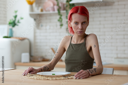 Fotografía  Red-haired anorexic woman sitting in the kitchen alone