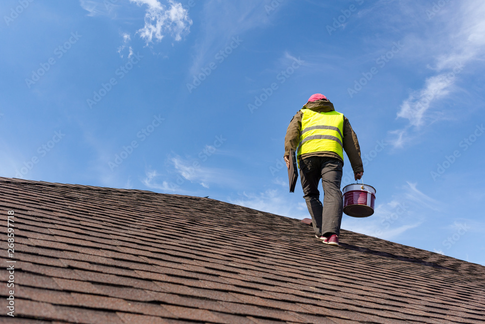Fototapety, obrazy: Workman standing on tile roof of new home under construction