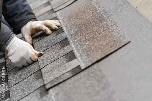 Fotografia Workman install tile on roof of new house under construction