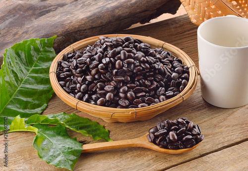 Coffee beans in wooden spoon on wood background