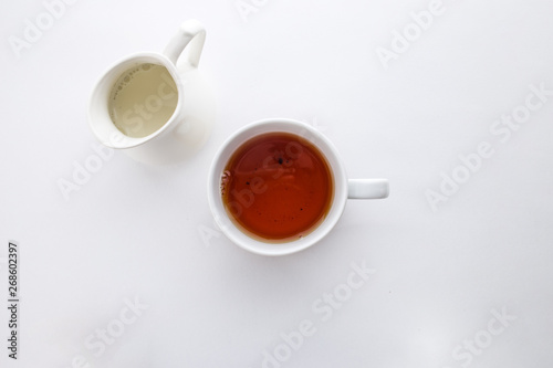 Fototapeta A cup of black tea with and milk jug isolated on white background top view obraz na płótnie