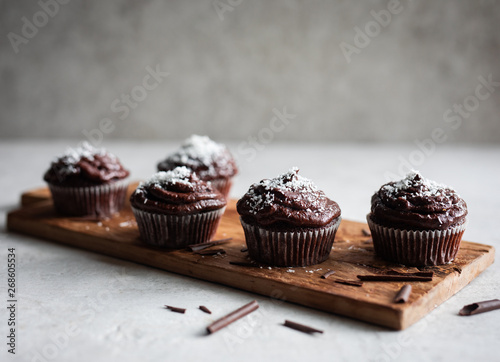 Chocolate cupcakes decorated with a chocolate cream frosting with coconut powder on top and chocolate shavings on a rustic wooden board on light background Canvas