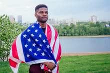 Handsome Afro American Man With United States Flag In Hands In Summer Park Near Lake Evening