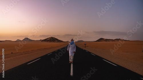 Keuken foto achterwand Marokko Man walking in a desert road in Sahara Desert during sunset