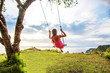 Leinwandbild Motiv woman swinging on a swing on a tropical island