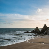 Stunning sunset landscape image of Westcombe Beach in Devon England with jagged rocks on beach and stunning cloud formations - 268618382