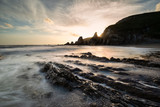 Stunning sunset landscape image of Westcombe Beach in Devon England with jagged rocks on beach and stunning cloud formations - 268618969
