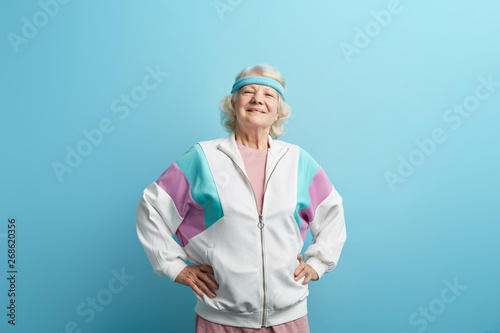 Photographie  Beautiful looking happy mature woman, smiling and enjoying life, wearing sweatshirt, isolated on purple background with copy space