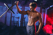 canvas print picture Portarait of handsome ripped caucasian bodybuilder man with naked torso posing with barbell in a gym with smoky red and blue background