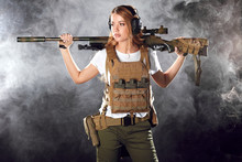 Skilled Blonde Female Soldier With Rifle In Hands Standing In Military Outfit In Smoky Darkness. Woman, Military Service And Firearm Concept