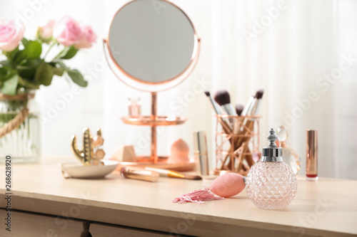 Fotografia Dressing table with different makeup products and accessories in room interior