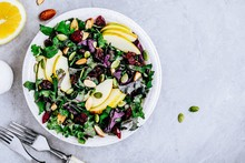 Apple Cranberry Kale Salad Bowl With Dry Cranberries, Almonds And Pumpkin Seeds.