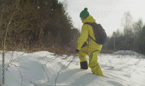Valokuva  Woman ecologist walking in a deep snow in the forest. Field work.