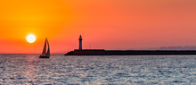 Panoramic View Of Ocean Sunset With Silhouettes Of Sailboat And Lighthouse Against The Orange Sky.