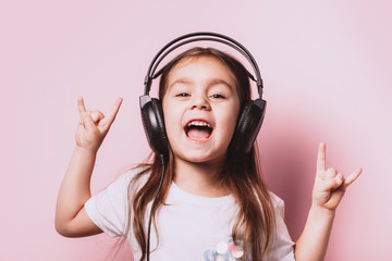 Cute little girl listening music wearing headphones on pink background. Funny emotions. Copyspace for text.