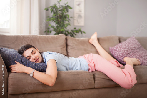 Obraz Tired funny young woman in summer everyday clothes stretches out and sleeps on sofa at home. Female student asleep in morning in living room after party, taking break for short sleep in middle of day  - fototapety do salonu