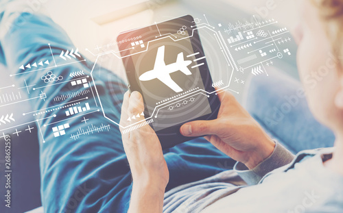 Airplane travel theme with man using a tablet in a chair Canvas Print