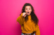 Leinwandbild Motiv Teenager girl over pink wall surprised and pointing front