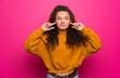 Leinwandbild Motiv Teenager girl over pink wall frustrated and covering ears