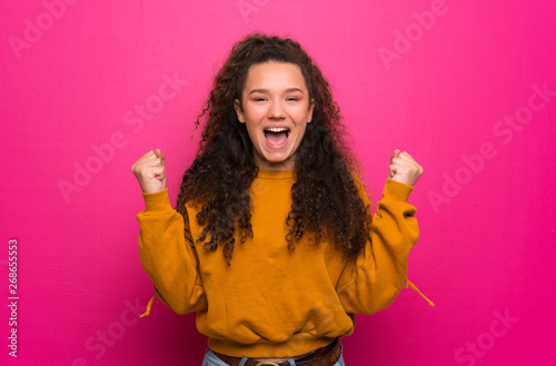 Fotografiet Teenager girl over pink wall celebrating a victory in winner position