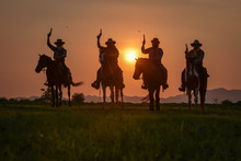 The Silhouette Of Four Men Wearing A Cowboy Dress With Horses And Guns Held In The Hand.
